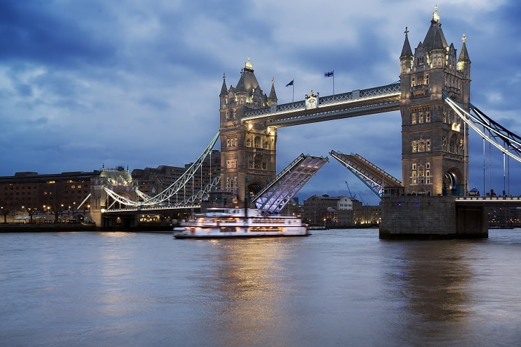 Landscape of Tower Bridge in London opening against a stormy sky with a boat passing under the cantilevers