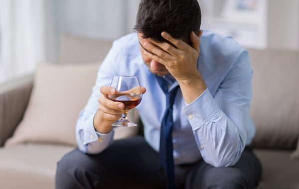 alcoholism, alcohol addiction and people concept - male alcoholic drinking brandy at home