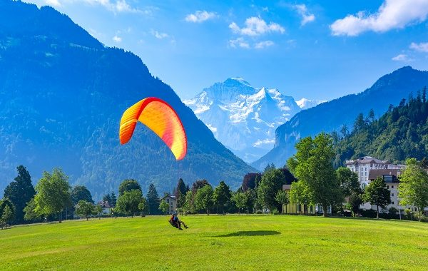 A paraglider landing at Hohematte Park in the center of Interlaken, important tourist center in the Bernese Highlands, Switzerland. The Jungfrau is visible in the background