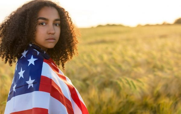 Sad depressed mixed race African American girl teenager female young woman with tears in her eyes in a field of wheat or barley crops holding and wrapped in USA stars and stripes flag in golden sunset evening sunshine